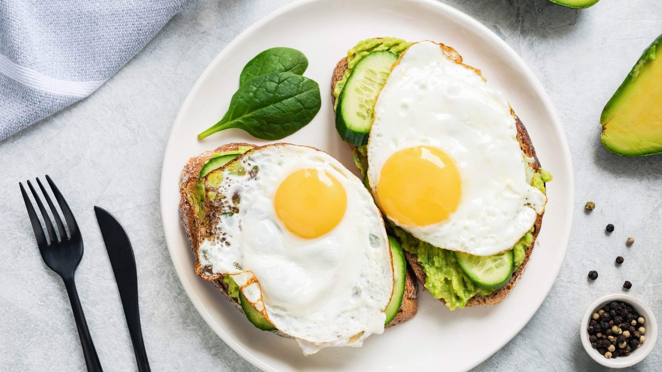 two slices of toast with avocado and sunny side up eggs on top