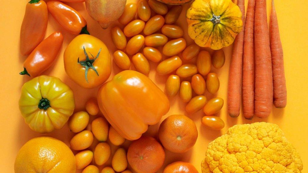 orange fruit and vegetables flatlay on orange background