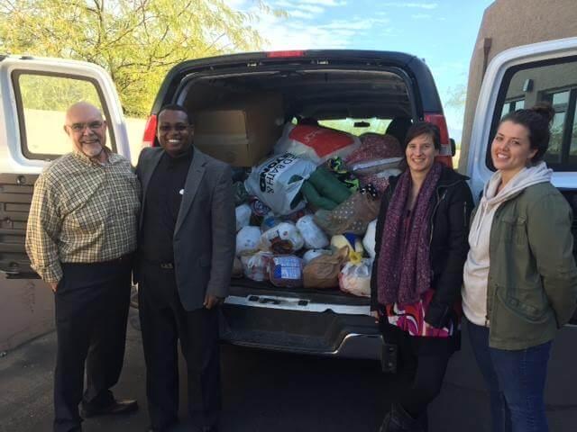 volunteers standing in front of van full of food donations