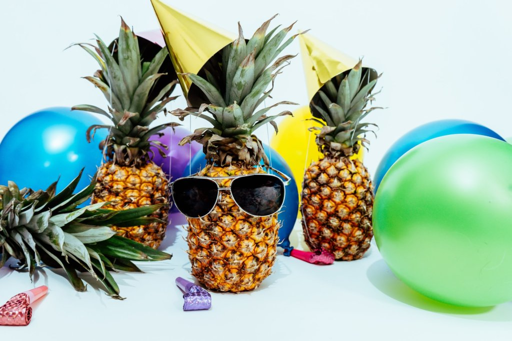 three pineapples with sunglasses and balloons