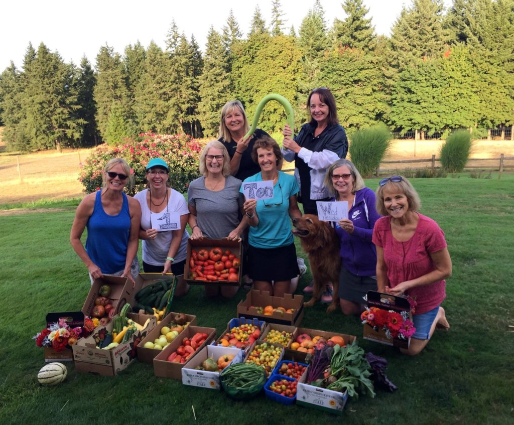 group of women posing with vegetable harvest