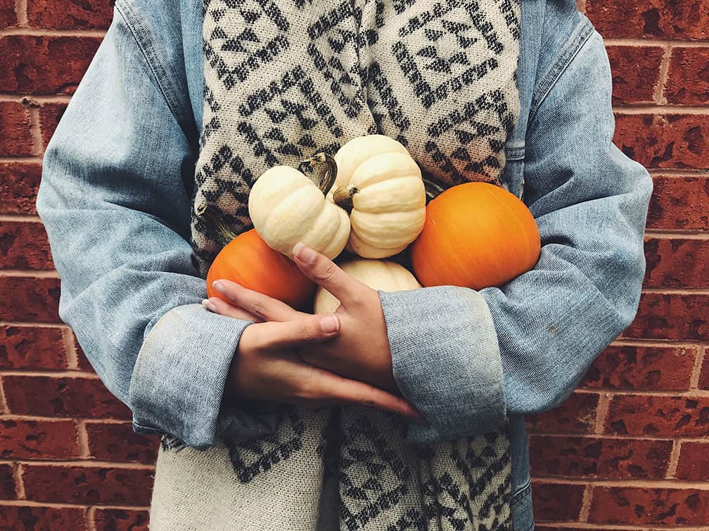 person holding five small pumpkins
