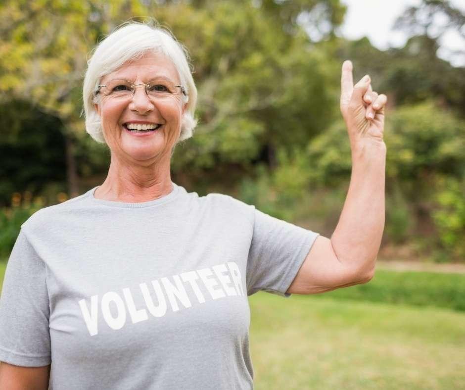 woman in volunteer shirt raising hand and smiling