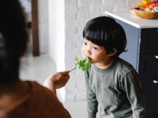 Child eating a leafy green vegetable