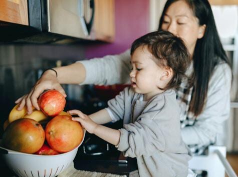 Mother and child filling a fruit basket