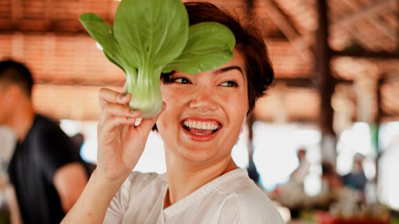 Woman smiling while holding a leafy vegetable